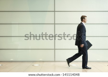 Side view of young businessman walking in passage of office - stock photo
