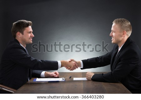 Side view of young businessmen shaking hands at desk against gray background