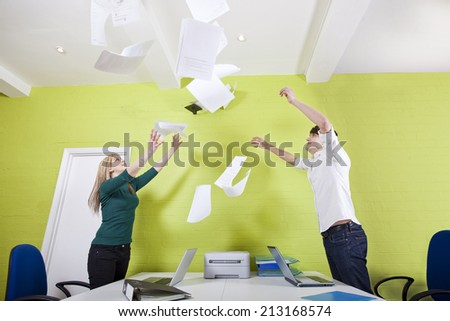 Side view of young businesspeople throwing documents in office - stock photo