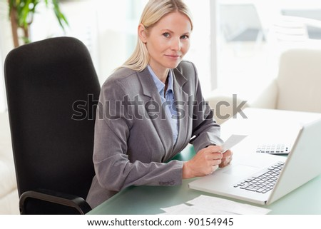 Side view of young businesswoman doing her accounting