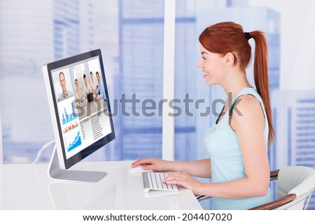 Side view of young businesswoman video conferencing with team on computer at desk in office - stock photo