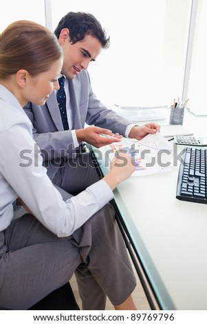 Side view of young colleagues doing paper work together - stock photo