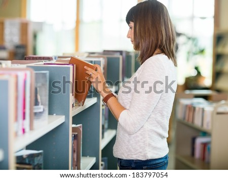Side view of young college student choosing book in bookstore - stock photo