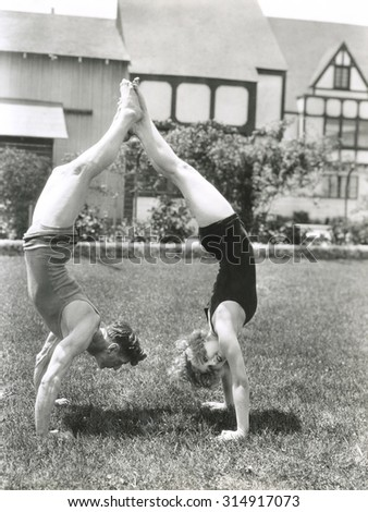 Side view of young couple doing handstands in yard