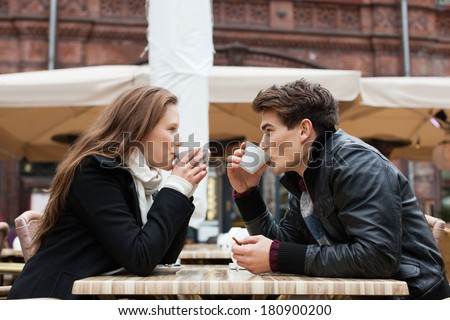 Side view of young couple drinking coffee together at outdoor restaurant - stock photo