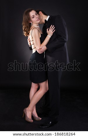 Side view of young couple embracing isolated over black background - stock photo