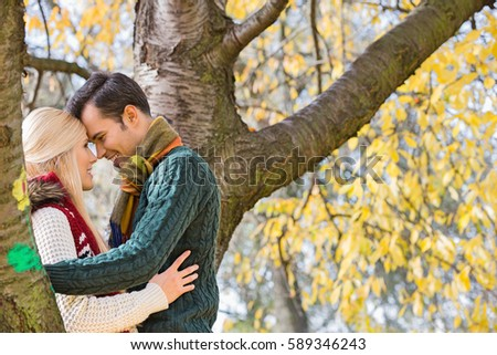 Side view of young couple hugging near autumn tree in park. Young Couple Hugging Stock Images  Royalty Free Images   Vectors