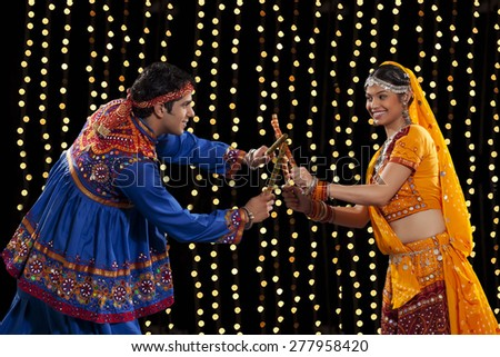 Side view of young couple in traditional wear performing Dandiya Raas against neon lights - stock photo