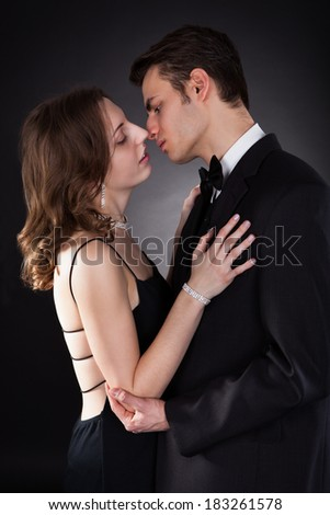 Side view of young couple kissing isolated over black background - stock photo