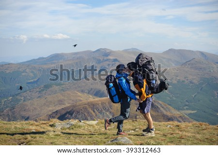 Side view of young couple on backpacking trip standing on mountain summit, kissing and enjoying the view of beautiful landscape against mountain background. Hiking gear/equipment.