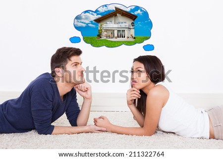 Side view of young couple thinking of dream house - stock photo