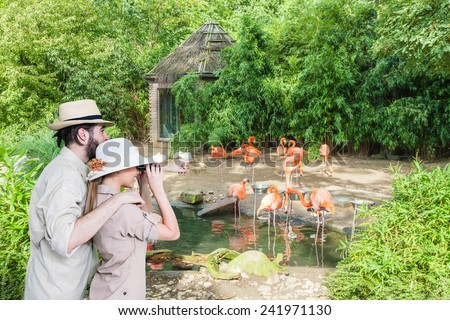 Side view of young, excited couple with binocular watching at pink flamingos.Copy space - stock photo