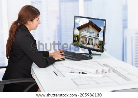 Side view of young female architect surfing house on computer at desk in office - stock photo