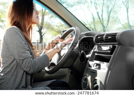 side view of young female driver use horn - stock photo