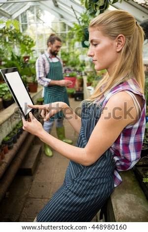 Side view of young female gardener using digital tablet at greenhouse