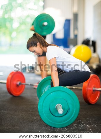 Side view of young fit woman picking barbell at healthclub - stock photo