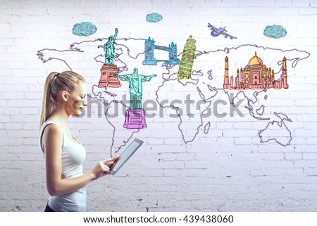 Side view of young girl using tablet against white brick wall with map and sights sketches. Travel concept - stock photo