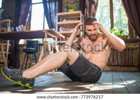 Side view of young male doing abdominal crunches in the living room. Workout at home, muscular man on floor working out on abdominal muscles.