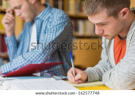 Side view of young male students writing notes at desk in the college library - stock photo