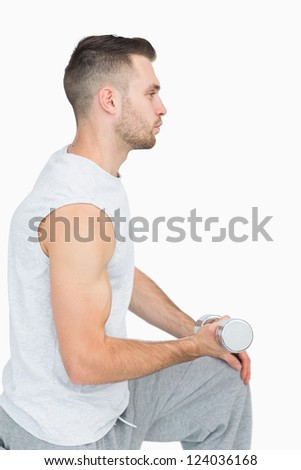 Side view of young man exercising with dumbbell over white background - stock photo