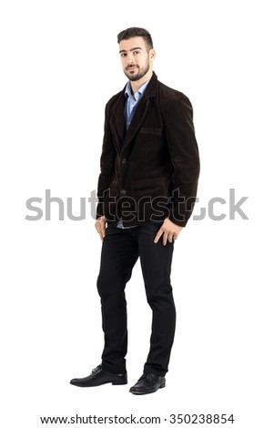 Side view of young man in corduroy jacket with thumbs in pockets. Full body length portrait isolated over white studio background.