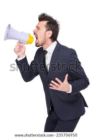 Side view of young man is making announcement over a megaphone on the white background.