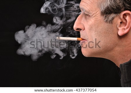 Side view of young man is smoking cigarette on black background. - stock photo