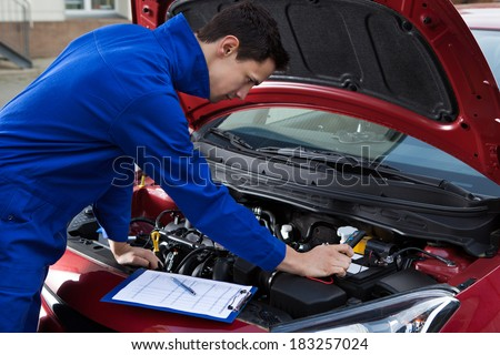 Side view of young mechanic in uniform repairing car - stock photo