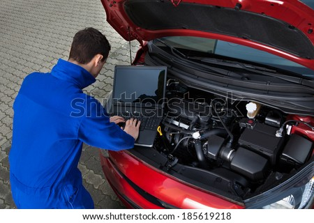Side view of young mechanic using laptop while repairing car on street - stock photo