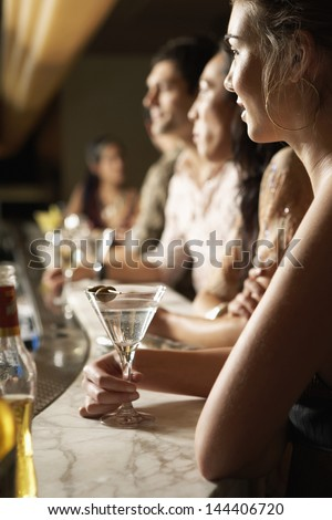 Side view of young multiethnic group at the bar with cocktail glasses - stock photo