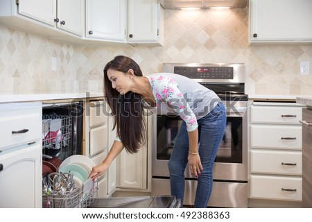 Side view of young pretty woman putting dishes into the dishwasher in her modern kitchen