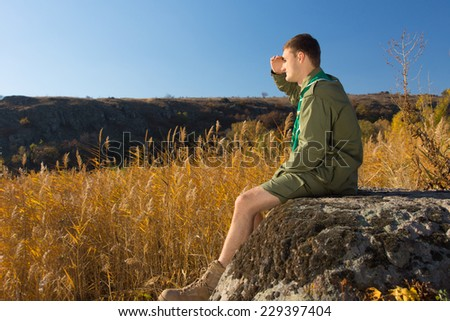Side View of Young White Boy Scout Sitting on Old Big Rock Watching Over the Wide Brown Field on an Autumn Season. - stock photo