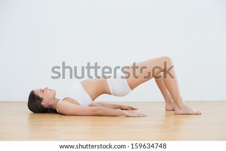 Side view of young woman doing the bridge pose in fitness studio