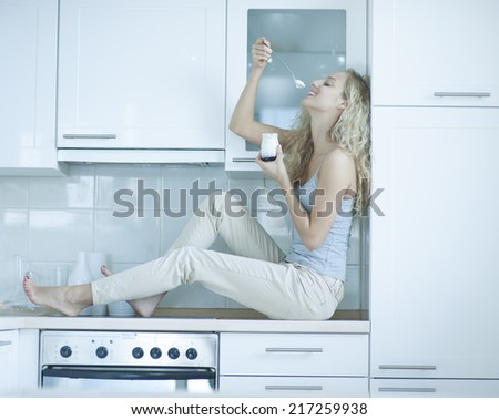 Side view of young woman eating yogurt while sitting on kitchen counter - stock photo
