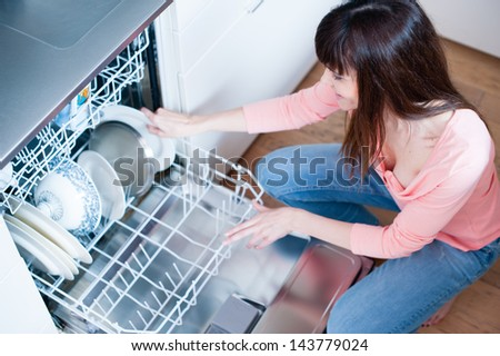side view of young woman in kitchen doing housework. middle aged girl in the kitchen using dishwasher - stock photo