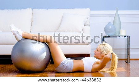 Side view of young woman in sportswear doing crunches in a living room.  Horizontal shot. - stock photo
