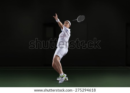 Side view of young woman in sportswear playing badminton isolated over black background - stock photo