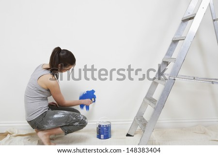 Side view of young woman painting wall with paintbrush at home - stock photo