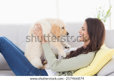 Side view of young woman playing with puppy while lying on sofa at home - stock photo