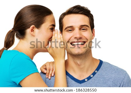 Side view of young woman sharing secret with man over white background. Horizontal shot.