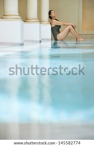 Side view of young woman sitting by swimming pool - stock photo
