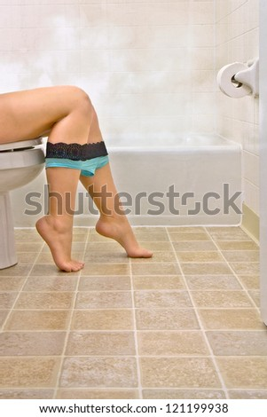 Side view of young woman sitting in bathroom - stock photo