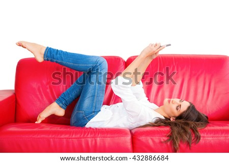 Side view of young woman taking selfie. Beautiful female is holding smart phone in front of her face. She is lying on red sofa isolated on white background.