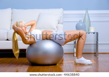 Side view of young woman wearing sportswear and doing crunches on a balance ball in living room.  Horizontal shot. - stock photo