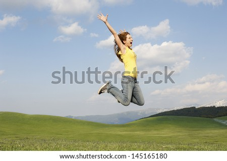 Side view of young woman with arms raised screaming while jumping in park - stock photo