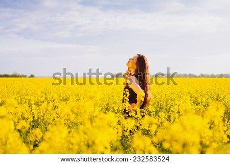 Side view of young woman with long hair touching her neck on yellow blooming rapeseed field - stock photo