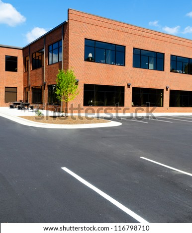 Side view on the generic red brick office building with parking lot - stock photo
