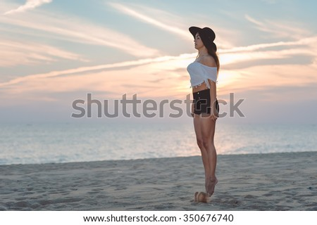 Side view photo of amazing brunette in floppy hat white top and shorts jumping in air on sandy beach copy space background at sunset