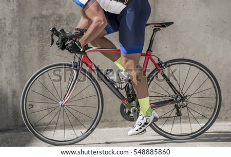 Side view photo of an attractive race biker, biking in front of a concrete wall. He pushes out of th saddle to speed up his bike.