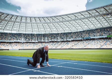 Side view photo of confident aged businessman lined up getting ready for race on modern sport track. Stadium as a background - stock photo
